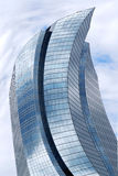 Distorted skyscraper. Distorted futuristic corporate building with glass walls reflecting clouds Royalty Free Stock Photo