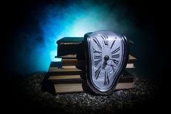 Distorted soft melting clock on a wooden bench, the Persistence of Memory of Salvador Dali. Time Concept. Distorted soft melting clock on the old books. With stock image