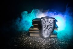 Distorted soft melting clock on a wooden bench, the Persistence of Memory of Salvador Dali. Concept. Distorted soft melting clock on the old books. With dark royalty free stock images