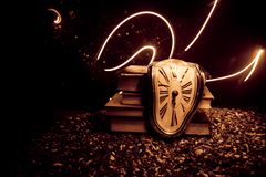 Distorted soft melting clock on a wooden bench, the Persistence of Memory of Salvador Dali. Time Concept. Distorted soft melting clock on the old books. With royalty free stock photo