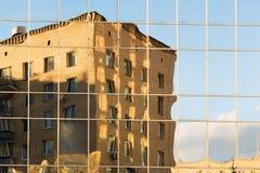 Distorted vred reflexion av ett tegelstenhus i fönstren av ett modernt glashus royaltyfri foto