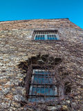 Distorted wall of an old stone building with two bar window pane Royalty Free Stock Photos