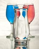 Distortion and refraction in three glasses of water. Three glasses of water showing reflections. Also distortion and refraction of light and alternating patterns Stock Photos