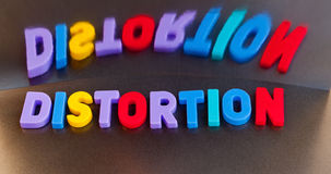 Distortion,. Text ' distortion ' in colorful upper case letters with wildly distorted inverted reflection  seen behind all on a dark background Stock Photo
