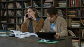 Distracción del estudiante que habla en el teléfono en biblioteca almacen de metraje de vídeo
