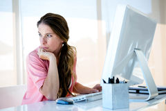 Distracted business woman looking away from her computer Stock Photography