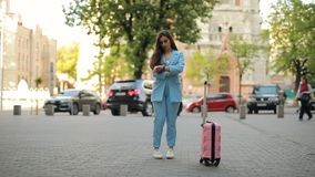 Distracted forgetful woman waiting taxi in city and forgets suitcase. Distracted forgetful woman waiting taxi in city and forget her suitcase stock video footage