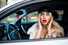 Distracted fright face of a woman driving car, wide open mouth eyes holding wheel side window view. Negative human face expression. Emotion reaction. Trip risk Royalty Free Stock Images