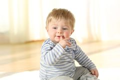Distracted kid biting a finger sitting on the floor. Portrait of a distracted kid biting a finger sitting on the floor royalty free stock photos