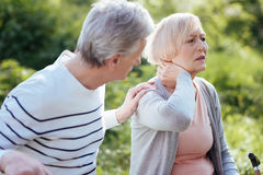 Distracted pensioner feeling terrible pain in the neck outdoors Royalty Free Stock Photos