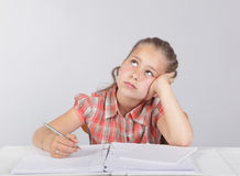 Distracted school kid at homework. Third-grade elemantary schoolchild girl supposed to make her homework or an assignmant but dreaming away and gazing into the Royalty Free Stock Photos