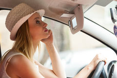 Distracted woman driving her car looking in mirror Royalty Free Stock Images