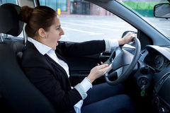 Distracted woman using smartphone and driving a car Stock Image
