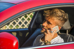Distracted Young Man Talking on Phone Driving. Inattentive Handsome Young Man Calling on Phone While Driving a Car Royalty Free Stock Image