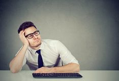 Distracted young man at working desk royalty free stock images