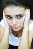 Distracted Young Woman. Portrait of a brunette young woman with her hands flat against each side of her head, her eyes averted to her left Royalty Free Stock Image
