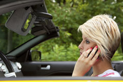 Distracted young woman driving. Distracted young woman talking on cell phone while driving Royalty Free Stock Images