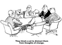 Distraction from Changing. Business cartoon of people in a meeting, including a cat, 'They hired a cat to distract them from thoughts of change Royalty Free Stock Photography
