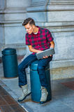 Distraction. Wearing a short sleeve, patterned shirt, jeans, boot shoes, holding a laptop computer, a young guy is sitting on a metal pillar, looking down at royalty free stock images