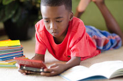 Distraction. A young African American boy laying on the floor playing video games instead of reading royalty free stock photos