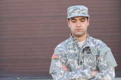 Distraught army soldier looking down.  stock photo