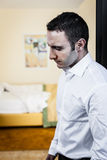 Distraught. An attractive but sad young man thinking in a hotel bedroom Royalty Free Stock Images