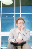 Distraught Businessman. One young businessman sitting down holding laptop on his knees in front of office building with one hand on chin Royalty Free Stock Photos