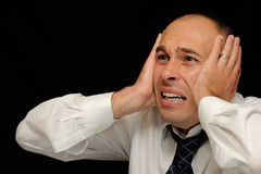 Distraught businessman. A portrait view of a distraught businessman as he holds his head with his hands Stock Photos