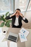 Distraught businessman at work looking up screaming in anger. Distraught businessman at work looking up screaming in anger, with report documents, laptop Royalty Free Stock Photo