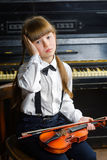 Distraught or distressed girl clutching her head and holding a violin Royalty Free Stock Image