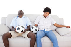 Distraught football fans sitting on the couch with balls Royalty Free Stock Images