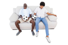 Distraught football fans sitting on the couch with balls Stock Photo