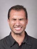 Distraught man's face. Studio portrait of a distraught man, closeup shot, gray background royalty free stock images