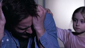 Distraught man crying in despair, grief in family, daughter supporting father. Stock footage stock video