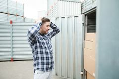 Distraught man at large container. Distraught shocked young man holding head in hands and standing near open cargo container outdoors stock photos