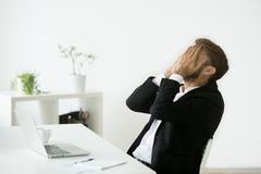 Distraught stressed bankrupt businessman covering face with hand. Distraught stressed businessman in suit covers face with hands feeling despair after business stock images