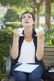 Distraught Young Woman with Pencil and Crumpled Paper in Hands. Frustrated and Upset Young Woman with Pencil and Crumpled Paper in Her Hands Sitting on Bench Royalty Free Stock Image