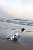 Distress message in a bottle on the deserted beach Stock Photo