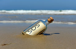 Distress message in a bottle on the deserted beach. Bottle found on the beach with a message inside Royalty Free Stock Photography