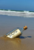 Distress message in a bottle on the deserted beach. Bottle found on the beach with a message inside Stock Photo