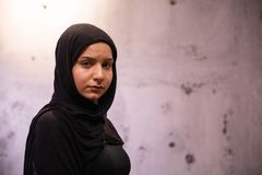 Distressed attractive Muslim female in a black hijab with a grungy damaged wall in the background