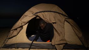Distressed black man crying in tent, homeless refugee ill and hungry in camp. Stock footage stock video