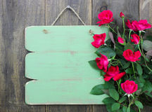 Distressed blank green sign with flower border of red roses hanging on rustic wood door Stock Image
