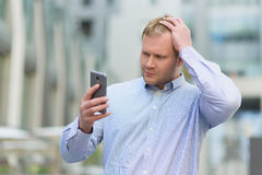 Distressed and confused businessman looking on his cell phone outdoors Royalty Free Stock Image