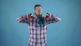 Distressed frozen man covered with frost in gloves and scarf on blue background shows finger down stock video