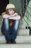 Distressed girl 2. Distressed girl is sitting on the stairs outside the door apartment Royalty Free Stock Photography