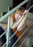 Distressed girl. Is sitting on the stairs outside the door apartment Stock Photo