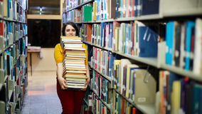 Distressed girl searching for books. Distressed female student wandering between shelves, searching for books royalty free stock photos