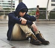 Distressed guy in a hoodie sitting outdoors Royalty Free Stock Photo