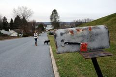 Distressed mailbox with blurry woman walking dog in background stock photos